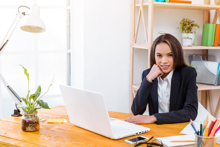 Beautiful young business woman in modern office with big window. Woman working with laptop and looking at camera
