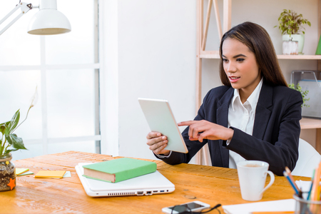 Beautiful young business woman in modern office with big window. Woman working with tablet computer Stock Photo