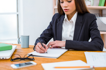 Beautiful young business woman in modern office with big window. Woman drawing up documents