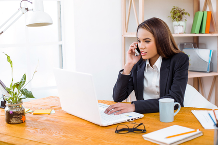 Beautiful young business woman in modern office with big window. Woman working with laptop and talking on phone