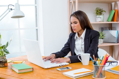 Beautiful young business woman in modern office with big window. Woman working with laptop Stock Photo