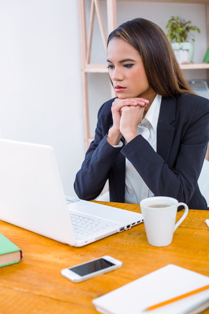 Beautiful young business woman in modern office. Woman working with laptop