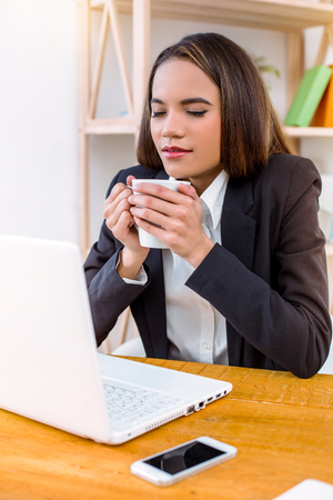 Beautiful young business woman in modern office. Woman working with laptop and drinking coffee