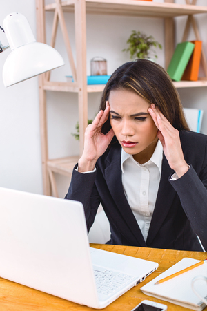 Beautiful young business woman in modern office. Tired woman with headache working with laptop
