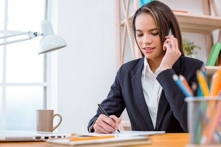Beautiful young business woman in modern office with big window. Woman drawing up documents and talking on phone