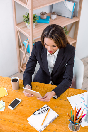 Top view photo of beautiful young business woman in modern office. Woman working with tablet computer