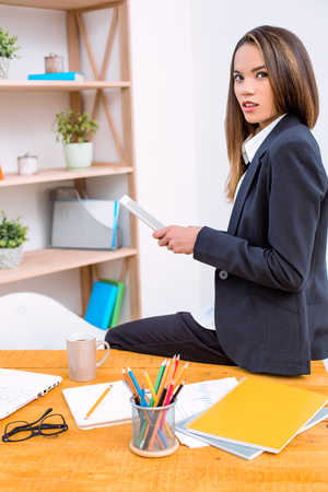 Beautiful young business woman in modern office. Woman sitting at table and working with tablet computer