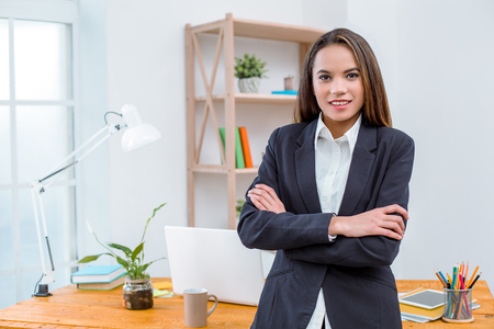 Beautiful young business woman in modern office with big window. Woman standing near table and looking at camera Stock Photo