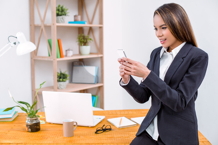 Beautiful young business woman in modern office. Woman standing near table and using mobile phone Stock Photo