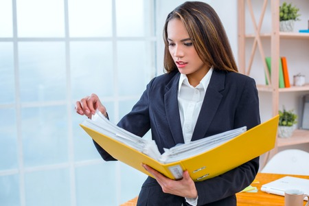 Beautiful young business woman in modern office with big window. Woman holding folder with documents