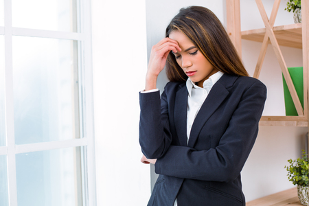 Beautiful young business woman in modern office with big window. Tired woman with headache Stock Photo