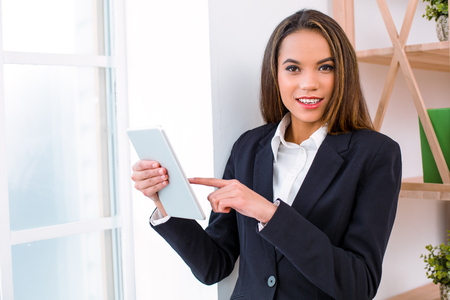 Beautiful young business woman in modern office with big window. Woman using tablet computer and looking at camera Stock Photo