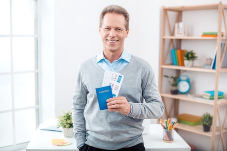 Stylish adult businessman while working day in office. Businessman looking at camera, holding tickets with passport and smiling. Office interior with bookcase and big window