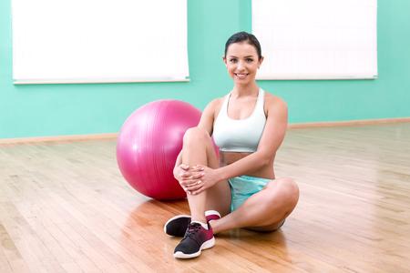 Foto der schönen jungen sportliche Frau. Fitness Mädchen sitzen in der Nähe von rosa Fitness-Ball in Sportverein. Frau lächelt und schaut in die Kamera