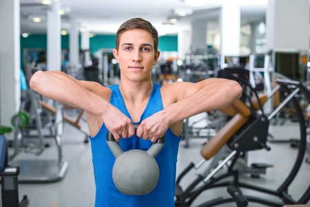 training device: Sportsman training with weight in sport club with exercise equipments. Man stretching and looking at camera Stock Photo