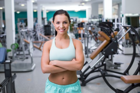 training device: Photo of beautiful young sporty woman. Fitness girl training in sport club with exercise equipments. Woman smiling and looking at camera Stock Photo