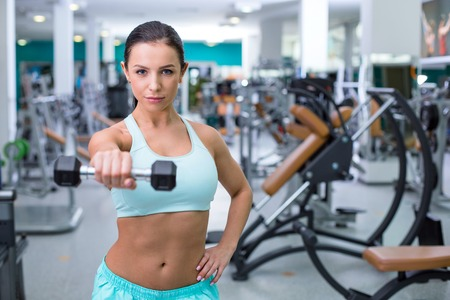 training device: Fitness girl training woth dumbbell in sport club with exercise equipments. Woman looking at camera. Focus on dumbbell