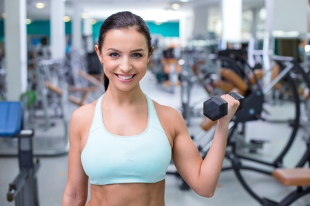 training device: Fitness girl training with dumbbell in sport club with exercise equipments. Woman smiling and looking at camera