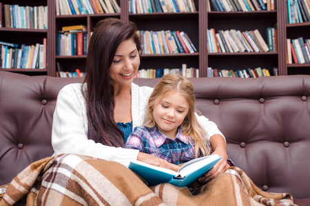 bedtime story: Photo of mother and little daughter. Nice cozy interior with big bookcase. Mother and daughter reading bedtime story