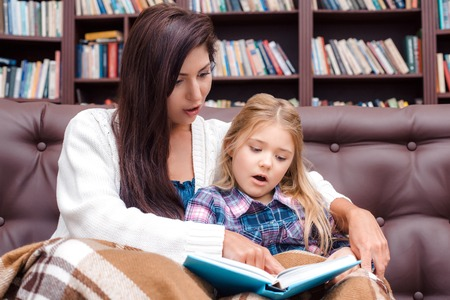 bedtime story: Photo of mother and little daughter. Nice cozy interior with big bookcase. Surprised mother and daughter reading bedtime story Stock Photo