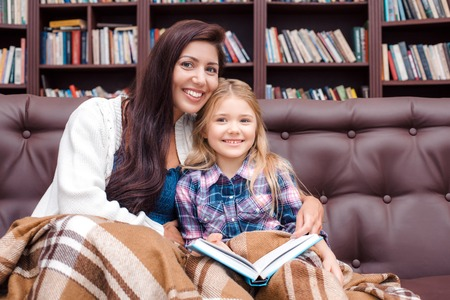 bedtime story: Photo of mother and little daughter. Nice cozy interior with big bookcase. Mother and daughter reading bedtime story, looking at camera and smiling Stock Photo