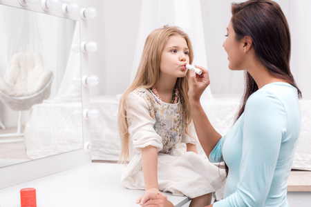 Young beautiful mother and little daughter while applying makeup. Nice cozy bedroom. Mother helping daughter to use lipstick