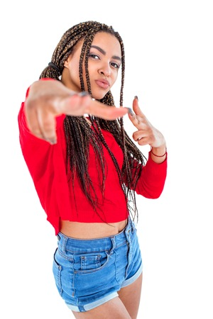 audacious: Funny picture of audacious african young woman. Girl with African braids looking at camera and making shooting gesture. Isolated background