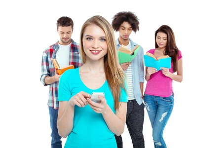 group shot: Studio shot of nice young multicultural friends. Beautiful people reading books. One girl using mobile phone, looking at camera and smiling. Isolated background