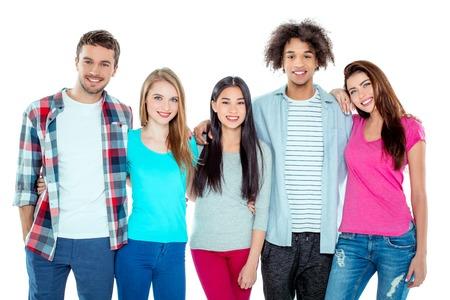 Foto de estudio de buenos amigos multiculturales jóvenes. Gente hermosa que mira la cámara, abrazándose y sonriendo. Fondo aislado