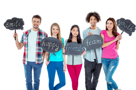 multicultural: Studio shot of nice young multicultural friends. Beautiful people looking at camera, holding nameplates with different words and smiling. Isolated background Stock Photo