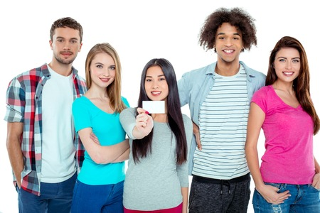Studio shot of nice young multicultural friends. Beautiful people looking at camera and smiling. One girl in the middle holding empty visit card. Isolated background