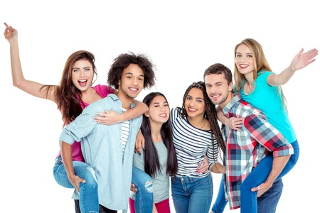 skin color: Studio shot of nice young multicultural friends. Beautiful people looking at camera and smiling. Two guys carrying girls piggyback. Isolated background