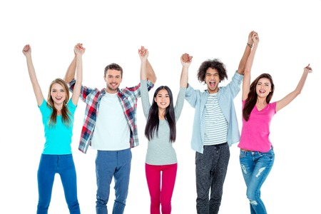 group shot: Studio shot of nice young multicultural friends. Beautiful people looking at camera, holding hands up and cheerfully smiling. Isolated background