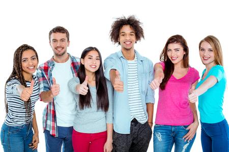 Estudio tirado de buenos amigos multiculturales jóvenes. la gente hermosa que muestra el pulgar hacia arriba, mirando a la cámara y sonriendo con alegría. fondo aislado