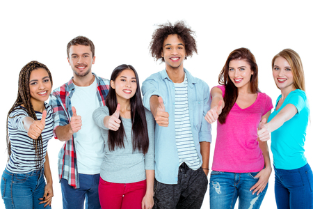 Studio shot of nice young multicultural friends. Beautiful people showing thumbs up, looking at camera and cheerfully smiling. Isolated background Stock Photo