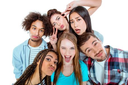 Lo studio ha sparato di belle giovani amici multiculturali. Bella gente divertirsi mentre facendo facce a porte chiuse. sfondo isolato Archivio Fotografico - 55490386