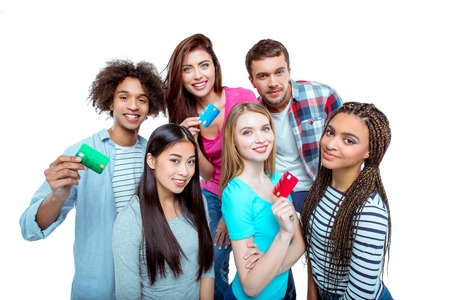 multicultural: Studio shot of nice young multicultural friends. Beautiful people holding credit cards, looking at camera and smiling. Isolated background