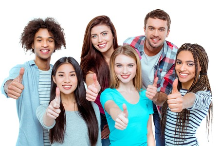 Studio shot of nice young multicultural friends. Beautiful people showing thumbs up, looking at camera and cheerfully smiling. Isolated background 免版税图像