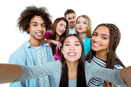 すてきな若い多文化友達のスタジオ撮影。美しい人元気に笑顔と selfie 写真をしながら楽しい時を過します。孤立した背景