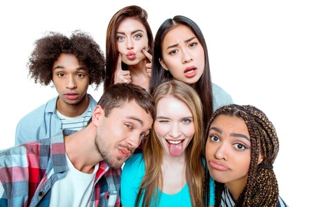 Studio shot of nice young multicultural friends. Beautiful people having fun while making faces at camera. Isolated background
