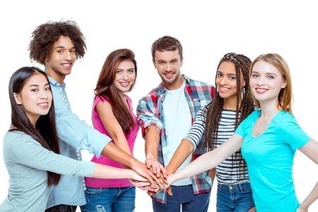 Estudio tirado de buenos amigos multiculturales jóvenes. la gente hermosa que pone la mano en la mano, mirando a la cámara y sonriendo con alegría. fondo aislado Foto de archivo