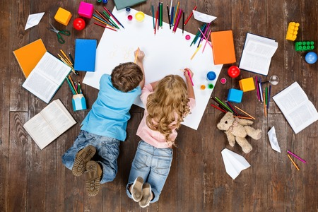 boy room: Happy children. Top view creative photo of little boy and girl on vintage brown wooden floor. Children lying near books and toys, and painting Stock Photo
