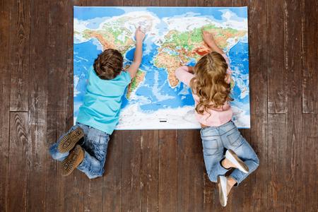 행복한 아이들. 상위 뷰 크리 에이 티브 사진 작은 소년과 소녀 빈티지 갈색 나무 바닥에. 세계지도에 누워있는 아이들