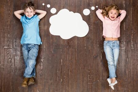 幸せな子供たち。トップ ビュー男の子とビンテージの茶色の木の床に女の子の創造的な写真。子供の考えと空の雲の近くに横たわって、カメラ目線