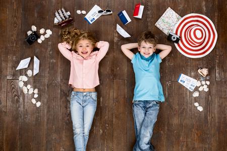 Glückliche Kinder. Draufsicht kreative Foto des kleinen Jungen und Mädchen auf Vintage-braunen Holzboden. Kinder liegen in der Nähe von Reise Dinge, Blick in die Kamera und lächelnd