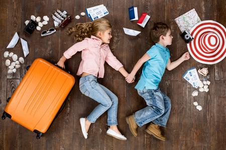 Glückliche Kinder. Draufsicht kreative Foto des kleinen Jungen und Mädchen auf Vintage-braunen Holzboden. Kinder liegen in der Nähe von Reise Dinge. Mädchen mit Koffer Standard-Bild