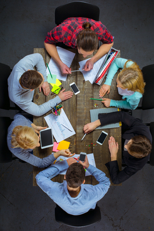 group shot: Top view creative photo of business people sitting at dark wooden vintage table. Business people having meeting. Concept for successful teamwork. There are electronic gadgets and graphics at table