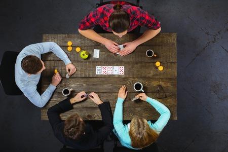 Vista superior de la foto creativa de amigos sentados en la mesa de la vendimia de madera oscura. Amigos que se divierten durante la reproducción de tarjetas Foto de archivo - 55491588