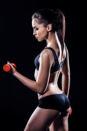 Donna attraente e sottile Lo studio ha sparato di giovane donna sportiva su priorità bassa nera. Addestramento della donna con il dumbbell Archivio Fotografico - 55580927