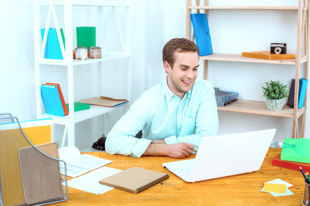 coder: IT company. Young programmer working with laptop. Nice office interier. Professional coder smiling